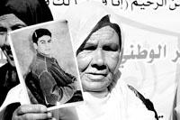 10月22日,一名巴勒斯坦妇女手持被关押在以色列监狱中的亲人的照片在加沙城参加集会,呼吁以释放在押巴勒斯坦人。新华社发