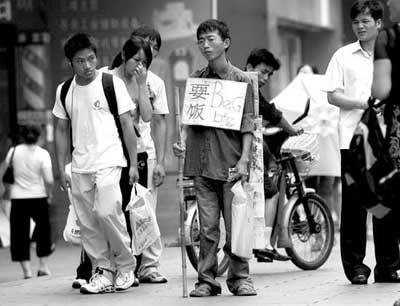 夏海波胸前挂着纸牌乞讨,引来路人好奇的目光