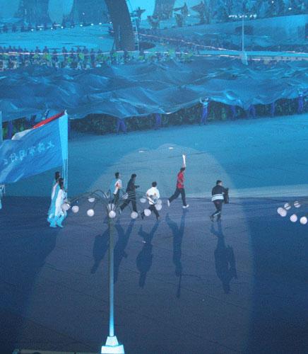 图文:六城会开幕式预演 模拟火炬手将火炬传递