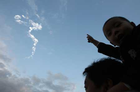 """图片说明:2007年10月24日,四川省西昌市卫星发射中心,火箭飞过留下一条""""龙型""""白烟。""""嫦娥一号""""于18时05分成功发射。"""