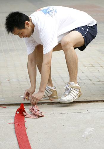 图文:朱启南生活照系列 为奥运试枪点燃鞭炮