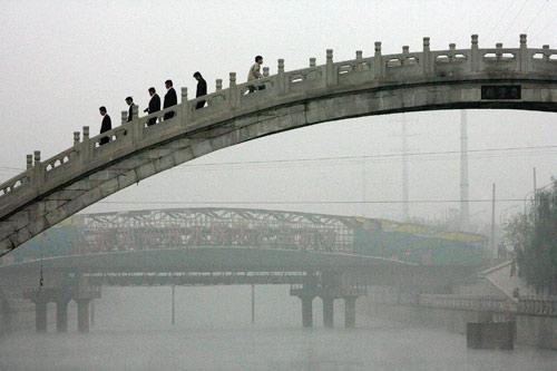 10月26日,北京,居民浓雾中穿越一座桥。