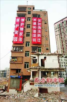 其中一家人在自家楼上挂起巨型条幅,抗议搬迁。本报记者 吴峻松摄