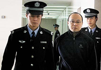 窦唯在执法人员的带领下准备进入法庭 摄/记者曹博远