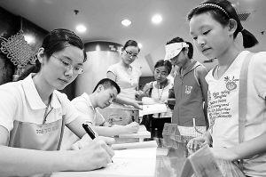 2007年8月21日,2007年北京高考理科状元、人大附中女生林茜(左)在北京王府井新华书店为读者签名售书。一帆摄