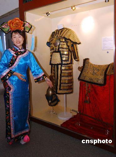 11月1日,身着旗装的沈阳故宫博物院讲解员介绍清高宗金索子锦面棉甲(左上)及累丝铁锭鎏金盔(左下)以及清皇帝御用仗马鞍(右起)。