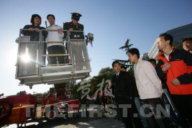 昨天,东城区地坛体育馆前,市民亲身体验了一把坐上专业消防高空云梯车升空的感觉