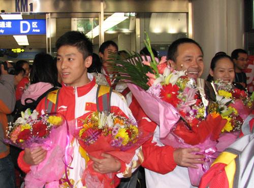 图文:中国蹦床队载誉而归 献花围绕新科冠军
