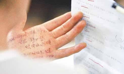 笔试中,一考生在偷看手上记的答案。可以看出他有多么紧张焦急了。(郑京烈/摄)