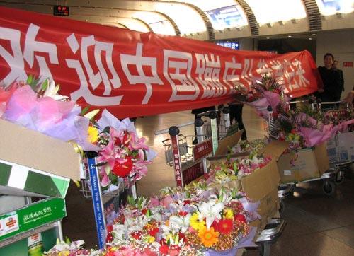 图文:中国蹦床队载誉抵京 现场精心布置迎选手