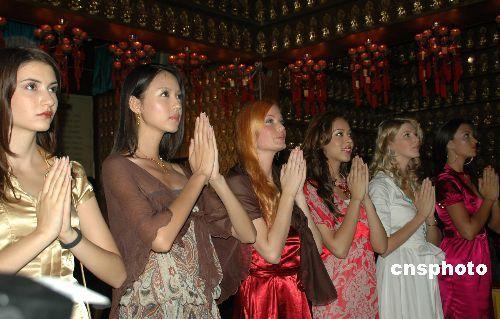 十一月五日,二十六名参加第五十七届世界小姐总决赛的佳丽来到三亚南山文化旅游区。图为佳丽们虔诚的拜佛。 中新社发 尹海明 摄