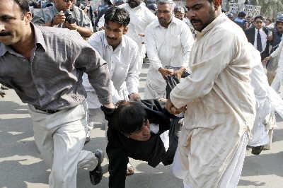 一名抗议的律师在将警察发射的催泪弹踢走后被逮捕。
