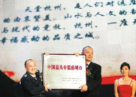 在杭州大剧院举行的颁奖仪式上,杭州平民英雄孔胜东(左)为杭州市长蔡奇颁奖。图片来源:今日早报 记者 胡元勇 摄
