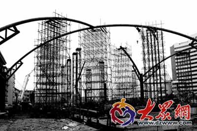 图为施工人员在暮色中争分夺秒进行钢结构雨棚上部网壳结构安装作业。