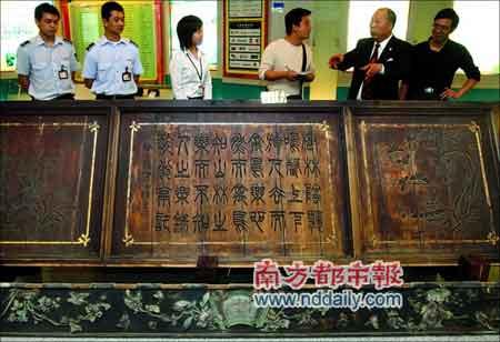 """捐赠者陈志伸先生(右二)向记者讲述""""雕篆书纹花鸟栏板""""的来历。"""