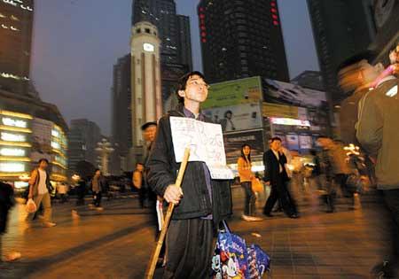 """昨日,解放碑,胸前挂着写有中英文对照""""要饭,beg life""""字样纸牌的夏海波,吸引着众多路人的目光 记者 陈诚 摄"""