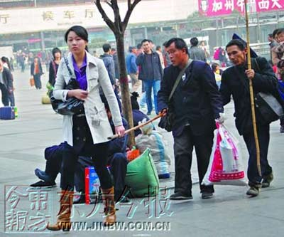 最美女大学生牵着两位盲人穿行在火车站广场