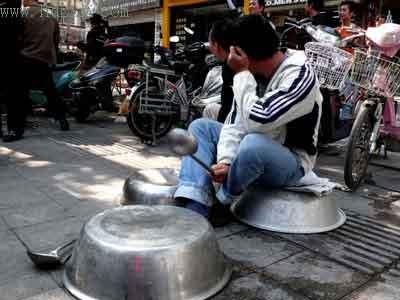 厨师坐店前敲打锅碗瓢盆抗议 孔瑜 图