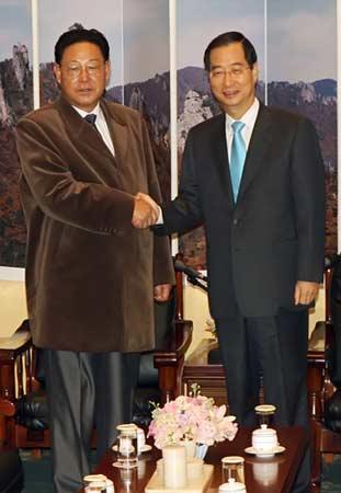 韩国总理韩德洙(右)14日上午在首尔华克山庄接待室里正在同前来出席第一次朝韩总理会谈的朝鲜总理金英日亲切握手。(韩联社图)