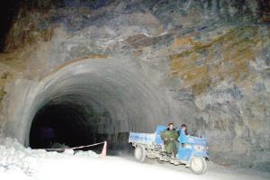一辆农用三轮车驶出隧道落石处。本报记者 周民 摄