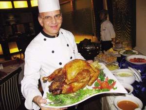 图为酒店工作人员向食客展示味道鲜美的火鸡