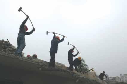 在爆破点附近,工人已进场进行旧房前期拆除 供图/《重庆晨报》