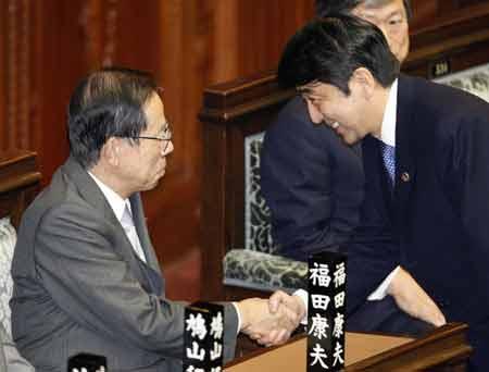 在11月13日举行的日本众议院全体会议上,安倍晋三(右)与福田康夫握手致意。 路透社