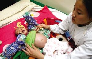 护士正在照顾被遗弃的女婴。本报记者 欧阳晓菲 摄