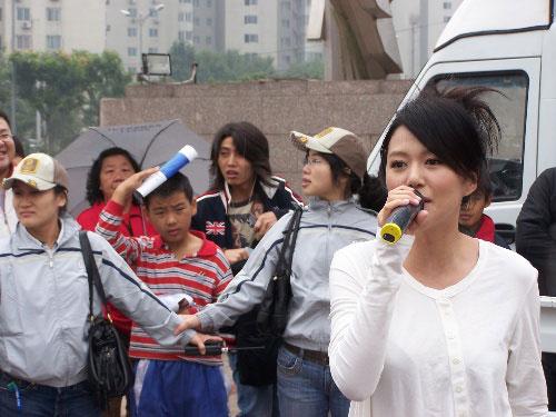 图文:助威团成员参与奥运活动 谭维维社区献唱