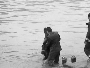 消防员蹚水并用衣服裹住裸女。 通讯员 熊李强 摄