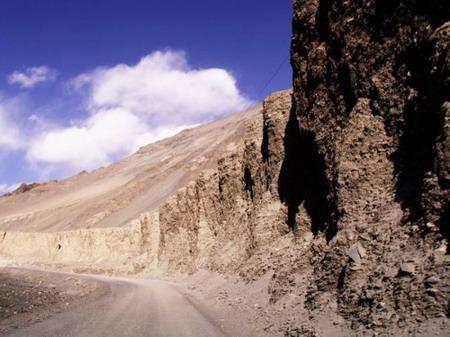 """公路一侧的山坡经过多年的风蚀就像""""魔鬼城""""一样"""