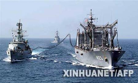 """2007年9月13日拍摄的这张资料照片显示的是正在阿拉伯海北部为一艘巴基斯坦驱逐舰添加燃料的日本""""常磐""""号补给舰(右)。据日本时事社报道,日防卫大臣石破茂11月1日下午下令撤回部署在印度洋的""""常磐""""号补给舰和""""雾雨""""号护卫舰。这两艘自卫队舰艇将于日本时间2日零时(北京时间1日23时)启程回国。新华社/法新"""