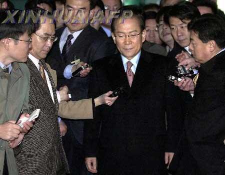 2003年12月15日,在韩国首都汉城,在野的大国家党前总裁、前总统候选人李会昌(中)在检察机关办公室外被记者团团包围。当日,李会昌因收取非法政治资金问题向韩国检察机关投案自首。新华社/法新