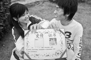 """照片:2007年11月7日,重庆市某大学校园内,领到爱情证书的情侣在展示自己的证书。近日,这种自娱自乐的""""爱情证书""""在一些高校受到校园情侣的青睐。陈诚摄"""