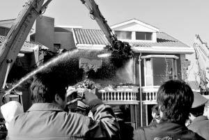 执法人员在拆除违建的别墅。本报通讯员 胡博 摄