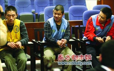 案犯魏某(中)和李某(右)对旁边获刑较轻的从犯(左)施以冷笑。本报记者冯宙锋摄