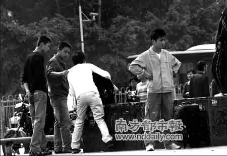 昨日上午,龙华汽车站广场,多名男子自称警察,分头围住两名带行李的男旅客,意图将他们带走。遭到拒绝后,一名男子强行拉扯。本报记者摄