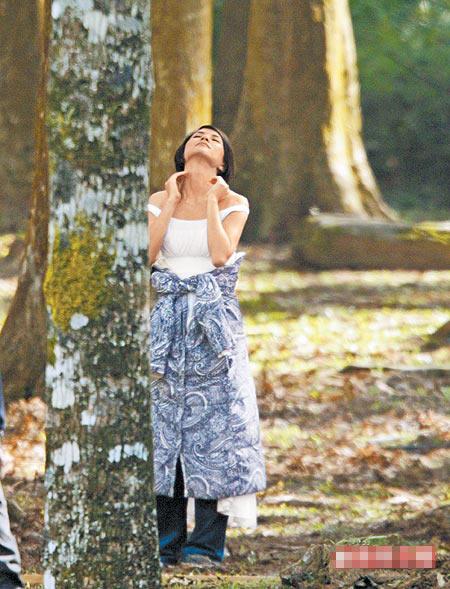 李心洁到惠荪林场拍广告,趁空档走到树旁,仰着头、抚着脖子享受芬多精,表情陶醉。