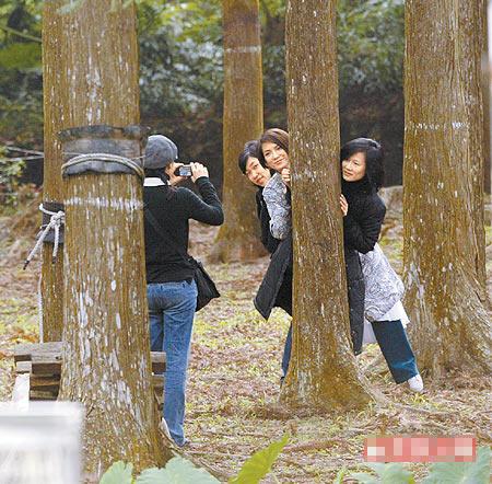 拍摄空档她(右二)与工作人员一同以树取景,找人帮忙拍照,3女摆出过时pose,笑得很开心。