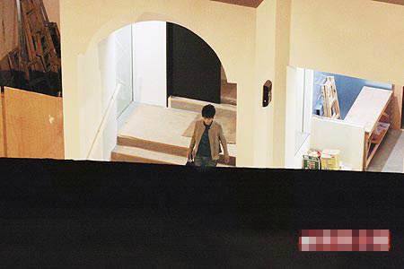 一名短发美女紧跟在梁朝伟身后,走出豪宅。