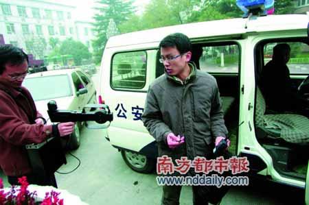 12月9日,在场外利用无线电对讲机传递答案的小江(持对讲机者),被便携式测向仪当场锁定。《华商报》供图