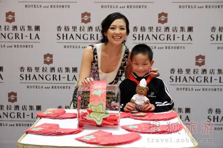 """章子怡和中国第一个家庭寄养儿童李胡冰一同在成都香格里拉大酒店为该酒店启动""""关爱儿童""""组织的慈善筹款项目。"""