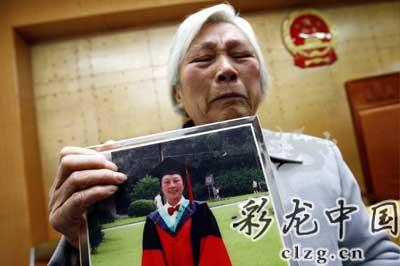 朱大妈抱着女儿的照片泣不成声 记者 王磊/摄