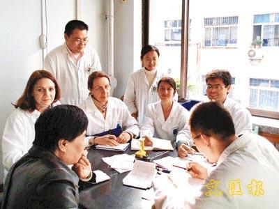由于中医在全球都享有盛誉,吸引了越来越多的境外学生赴华拜师学艺。图为山东中医药大学的师生们在进行学术讨论。(香港《文汇报》)