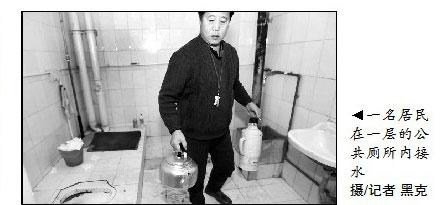 ▲一名居民在一层的公共厕所内接水