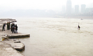 小伙站在江心,等待救援。