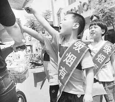 """在今年""""世界无烟日"""",河南省汤阴县几名小学生身披写有""""吸烟有害健康""""字样的绶带,向市民进行宣传。常中正摄"""