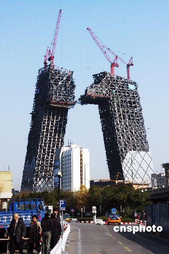 """11月18日,在北京中央商务区(CBD),由两个巨大楼宇组成的中央电视台新楼正在加紧施工。据悉,两座大楼将于12月份正式对接,不久这对""""情侣""""将在空中""""拥抱""""构成一个整体。"""