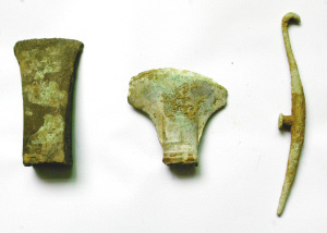 现场发掘出的三件青铜器:斤(左)、钺(中)、带钩(右)