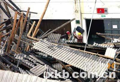 倒塌厂房内部一片狼藉,一名工作人员在勘查.